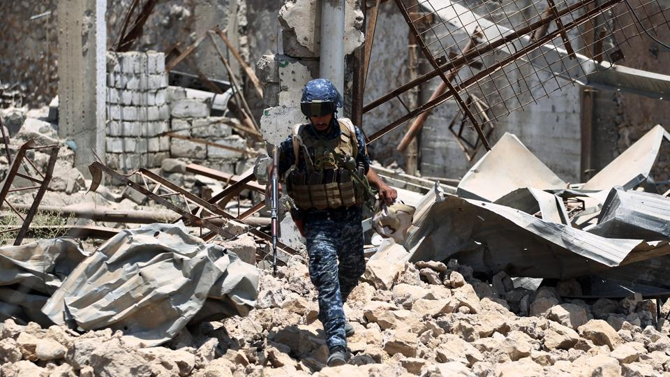 A member of the Iraqi forces walks amidst the rubble during their advance towards Mosul's Old City on June 18, 2017.