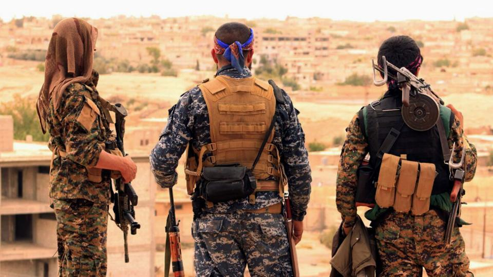 This April 30, 2017, file photo provided by the Syrian Democratic Forces (SDF) shows fighters from the SDF looking toward the northern town of Tabqa, Syria. The U.S.-led coalition headquarters in Iraq said in a written statement that a U.S. F-18 Super Hornet shot down a Syrian government SU-22 on Sunday, June 18, after it dropped bombs near the U.S. partner forces, known as the Syrian Democratic Forces. The shootdown was near the Syrian town of Tabqa.