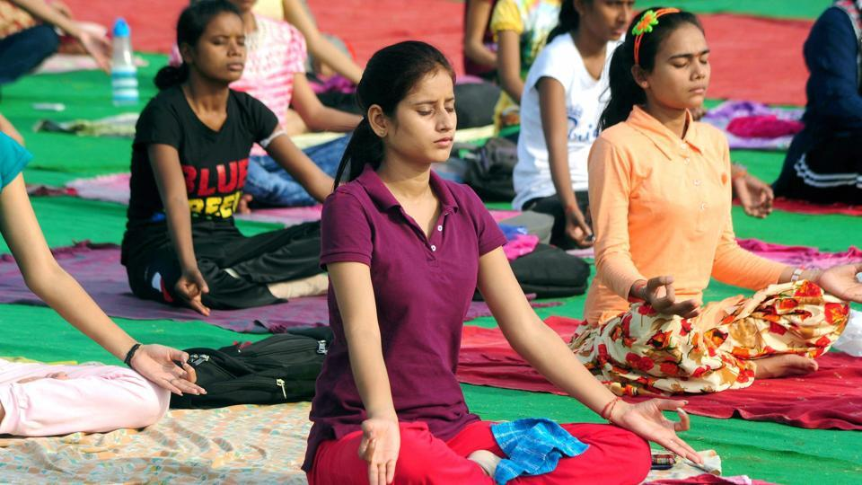 Students practice yoga ahead of the third International Yoga day on June 21 at Parade Ground in Allahabad on Saturday.
