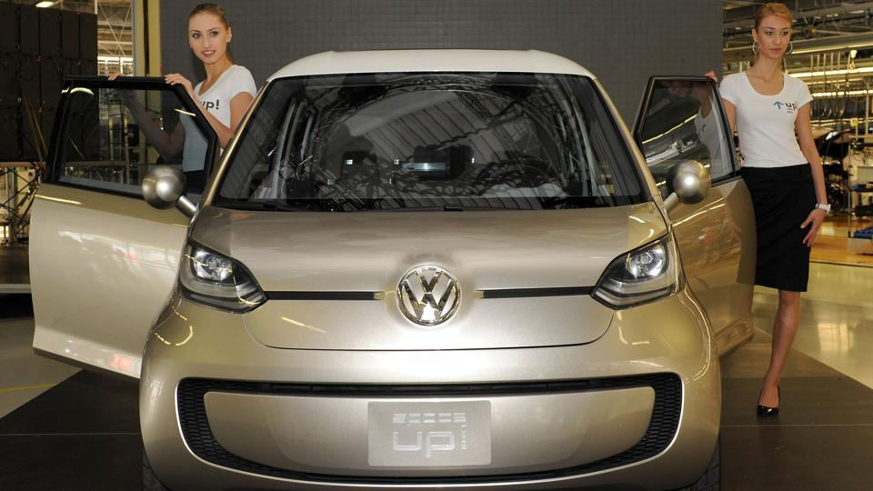 This file photo shows models posing in front of a new Volkswagen UP! car during an official presentation of the New Small Family vehicle production at the Volkswagen car manufacturing plant in Bratislava, Slovakia.