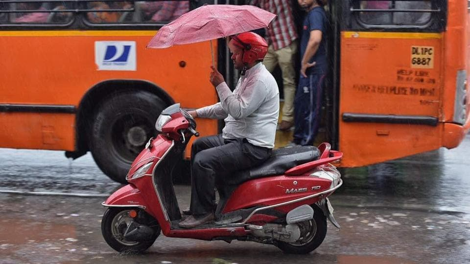 A motorist manoeuvres his morning commute with a skilful display using an umbrella. (Raj K Raj/HT Photo)