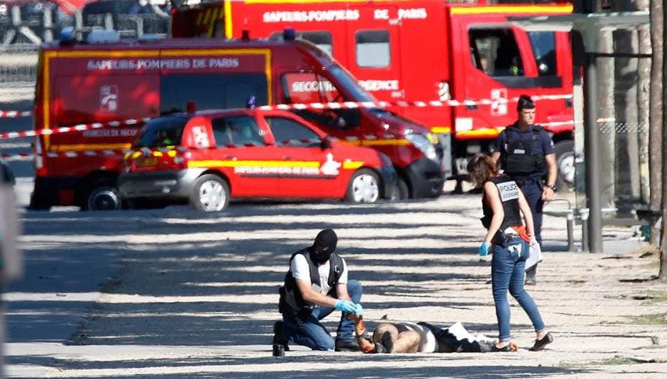 Criminal police inspect the body of a suspect at the scene of an incident in which a car rammed a gendarmerie van on the Champs-Elysees Avenue in Paris, France, June 19, 2017.