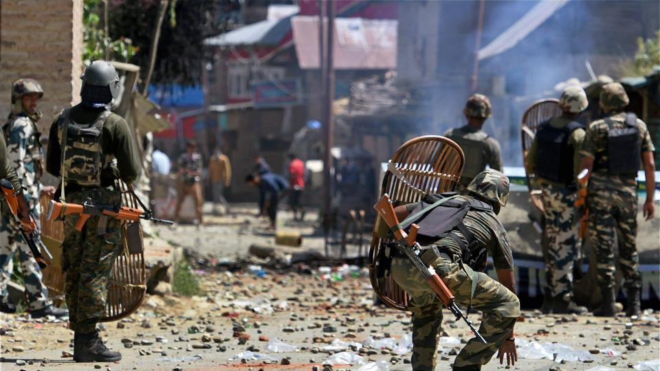 Anantnag: CRPF jawans chasing protesters throwing stones on them during a protest at Arwani village of Anantnag district of South Kashmir on Friday. PTI Photo by S Irfan (PTI6_16_2017_000219B)