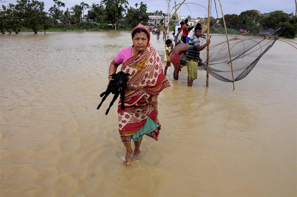 A woman walks to safe place as many others catch fish at the flooded village of Srilanka Basti in Agartala on Tuesday.