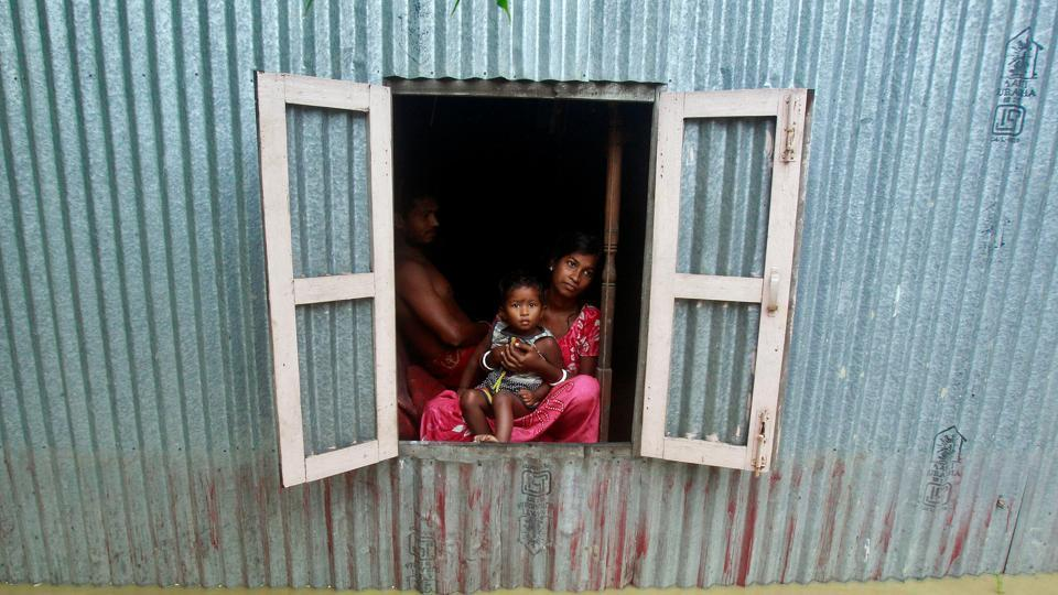 A woman and a child look outside from a window of their house at a flooded village on the outskirts of Agartala.