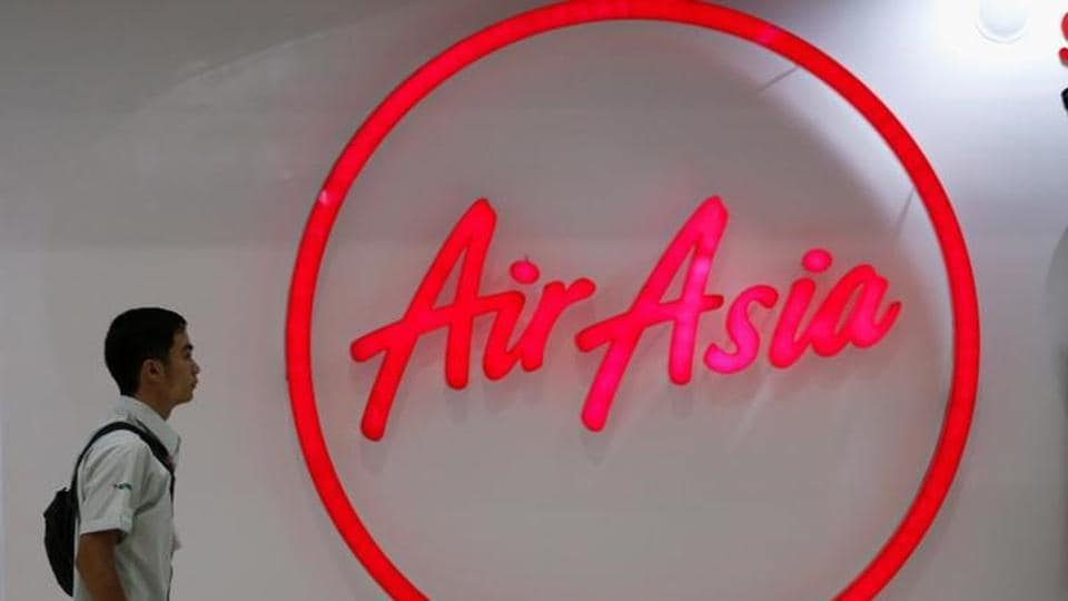 A man walks past the logo of AirAsia at Don Muang International Airport in Bangkok.