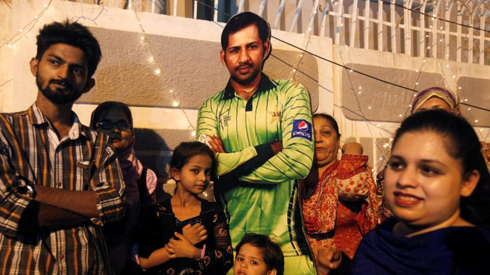 Fans pose with a picture of Sarfraz Ahmed, the captain who helped Pakistan secure the treble of ICC Championship trophies. (REUTERS)