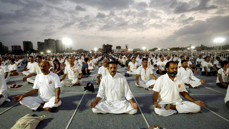 People practice asanas during a mass yoga session on the third day of Baba Ramdev Yoga camp in Ahmedabad, Gujarat on June 20, 2017. (PTI)