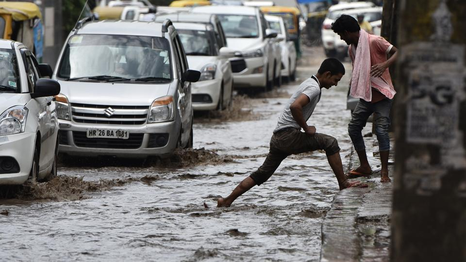 Vehicles pass through the waterlogged Sector 15, in Gurgaon, on Tuesday.