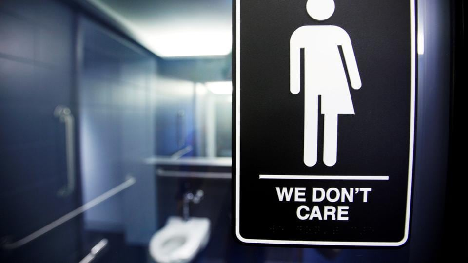 A sign protesting a recent North Carolina law restricting transgender bathroom access adorns a bathroom stalls at the 21C Museum Hotel in North Carolina. Several offices in India are revamping their policies to make the space more welcoming and inclusive of transgenders.
