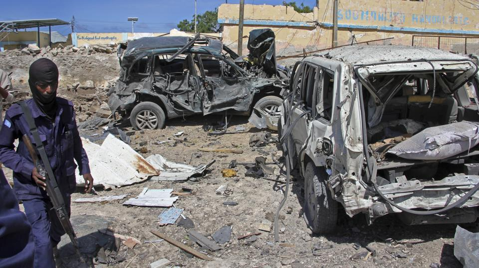 A Somali soldier walks past destroyed vehicles at the scene of a car bomb attack in Mogadishu, Somalia Tuesday, June 20, 2017.