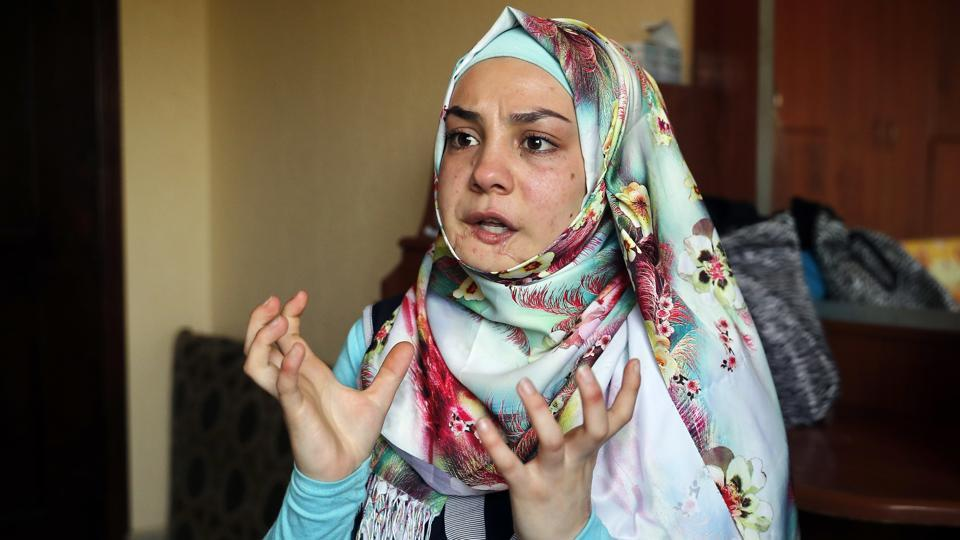 Alaa, 19, who was shot in her jaw  during a clashes between the Syrian government forces and the rebels gestures as she tells her story.  (AP)