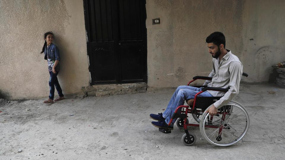 Adnan(R), 19 who was shot in the spine from a sniper in 2013 as he was crossing a bridge on his bike to bring bread to his family in Homs province, pushes his wheelchair at a small alley  back to his home. Adnan is now paralyzed from the waist down although operations and physiotherapy enabled him to strengthen his upper body to adjust to the new life. (AP)