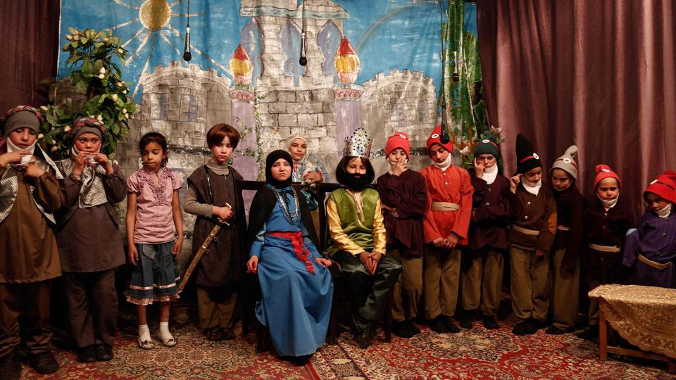 A group picture shows Syrian girl actors posing after performing an English-language school play adaptation of Snow White and the Seven Dwarfs. To escape the nightmare of life in their besieged home town near Syria's capital, 13 young girls sought refuge in a fairytale performance of Snow White and the Seven Dwarfs. (AFP)
