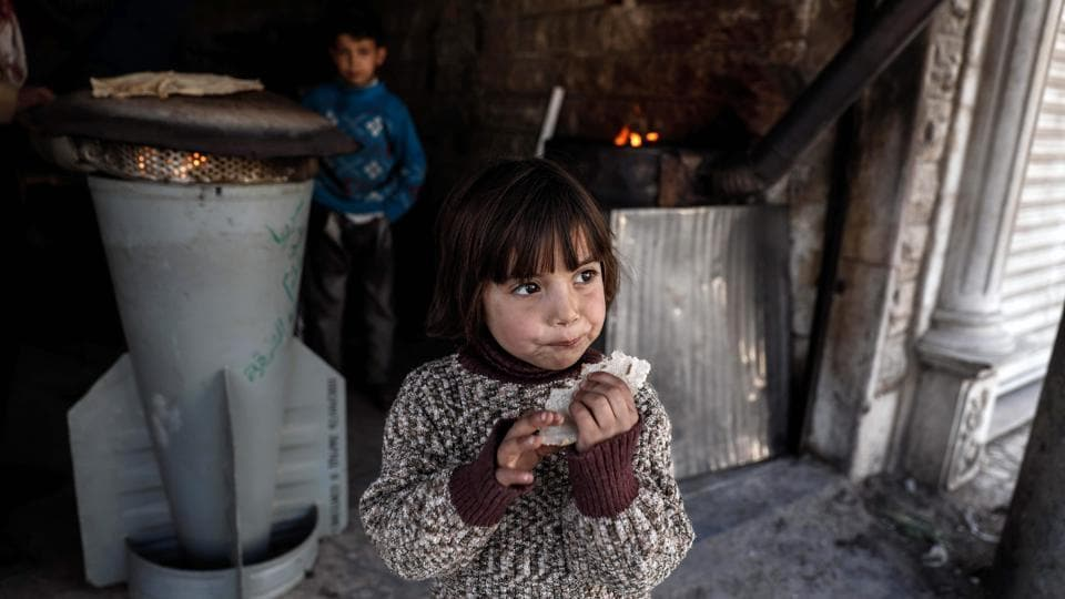 A Syrian girl eats a bread which was baked in a makeshift oven using the remains of a rocket on the eastern outskirts of the Syrian capital, Damascus. After six years of conflict, Syrians are facing one of the largest humanitarian crisis in the world with children having paid the ultimate price. According to UNICEF, 2016 was the worst year for Syrian children with more 600 reported dead. Nearly 6 million children are estimated to be dependent upon humanitarian assistance with most of them suffering from war-related trauma in Middle East's conflict zone.  (AFP)