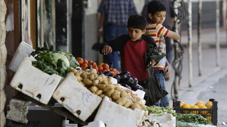 Children buy vegetables at the town of Madaya in the Damascus countryside.  (AP)
