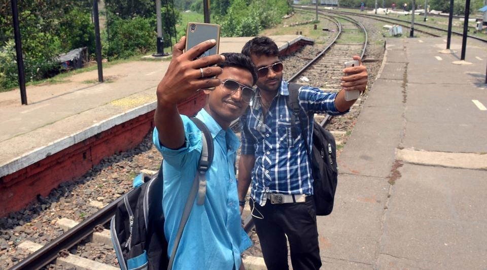 Students taking selfie at railway station.