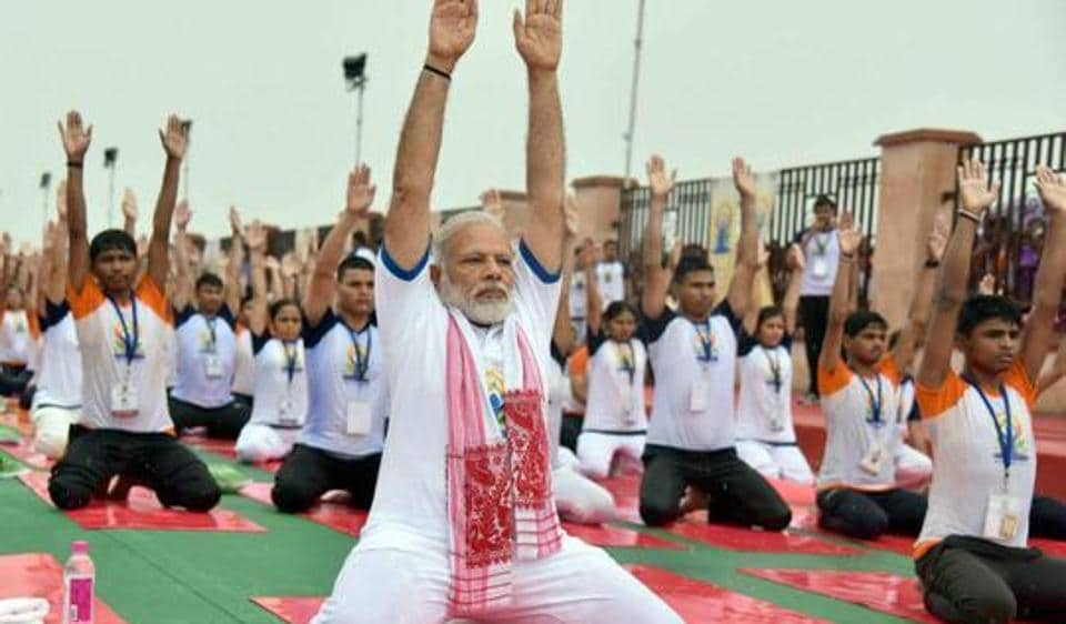 Prime Minister Narendra Modi performs yoga along with thousands of others during a mass yoga event on 3rd International Yoga Day in Lucknow.