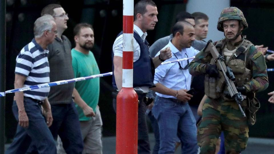 Soldiers and police officials guide members of the public from inside a cordoned off area on a street outside Gare Centrale in Brussels on June 20, 2017, after an explosion in the Belgian capital.