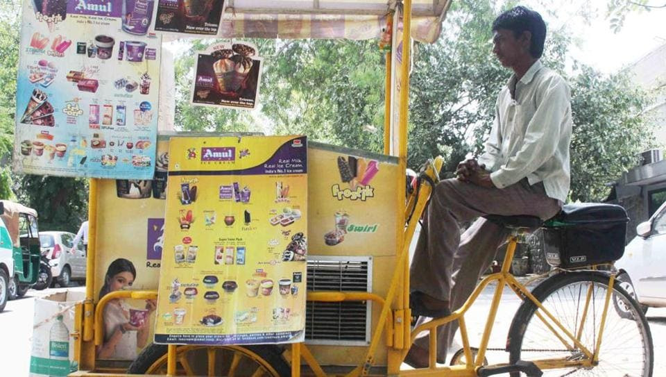 Bimal's cart is painted yellow. It has posters advertising various ice creams.