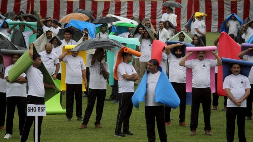 BSF Personnel use yoga mats to protect themselves from rainfall during a group session on International yoga day, in Jammu, Jammu and Kashmir. (Nitin Kanotra/HT Photo)