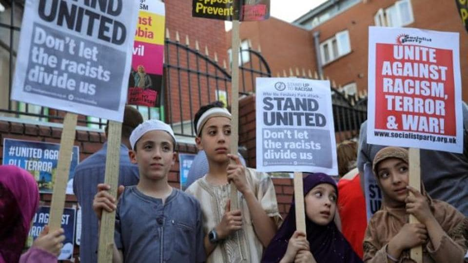 """Locals sang together and laid flowers at the mosque, holding up placards which said """"Don't let the racists divide us"""" and """"No to Islamophobia, No to War""""."""