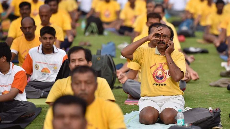 A man speaks on the phone while occupied with a yoga pose on an International Day of Yoga session at Kanteerava Stadium in Bengaluru, Karnataka. (ARIJIT SEN/HT Photo)