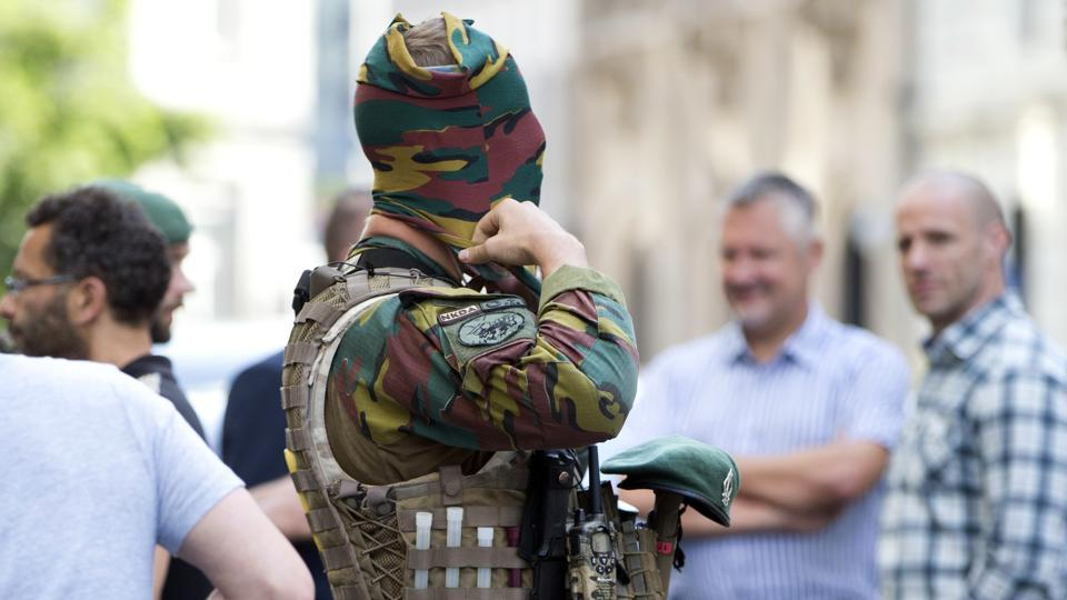 A Belgian Army soldier adjusts his face mask as he patrols outside the prime ministers office in Brussels on Wednesday, June 21.