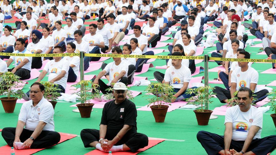 (From left) Union health minister JP Nadda , Punjab governor VP Singh Badnore and Chandigarh BJP  chief Sanjay Tandon performing bhadrasana during a yoga session at the Sector 17 Plaza  in Chandigarh. (Keshav Singh/HT)