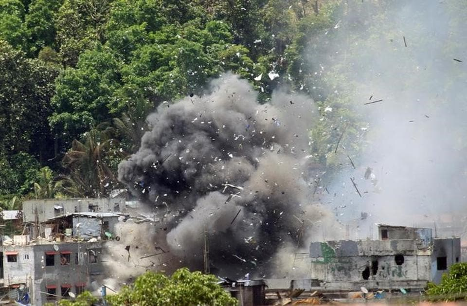 Debris and smoke are seen after an OV-10 Bronco aircraft released a bomb during an airstrike, as government forces continue their assault against insurgents from the Maute group, who have taken over large parts of Marawi City, Philippines, June 20.