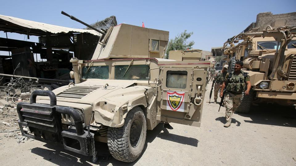 Members of the Iraqi forces walk past parked humvees and armoured vehicles during the advance towards the Old City of Mosul as the ongoing offensive continues to retake the last district still held by the Islamic State (IS) group.