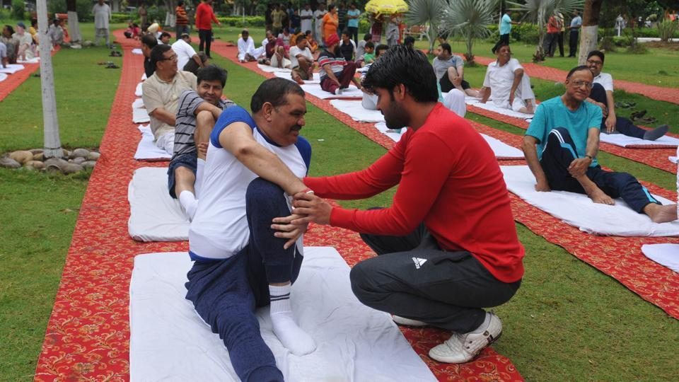 A yoga instructor lends a helping hand as Union minister Vijay Sampla attempts the Vakrasana in Jalandhar. (Pardeep Pandit/HT )