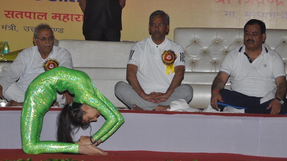 CM Trivendra Singh Rawat (centre) looks on as a child performs on the occasion of International Yoga Day at Parade Ground in Dehradun on Wednesday.