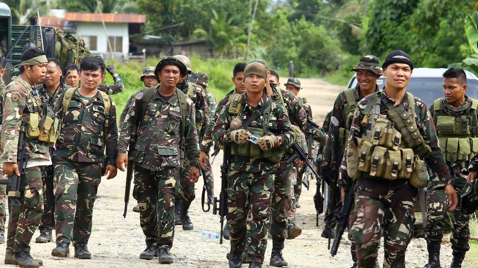 Philippine soldiers patrol a road at Pigkawayan, a farming town about 160 kilometres (100 miles) from Marawi city, on north Cotabato, in the southern Philippine island of Mindanao on June 21, 2017.