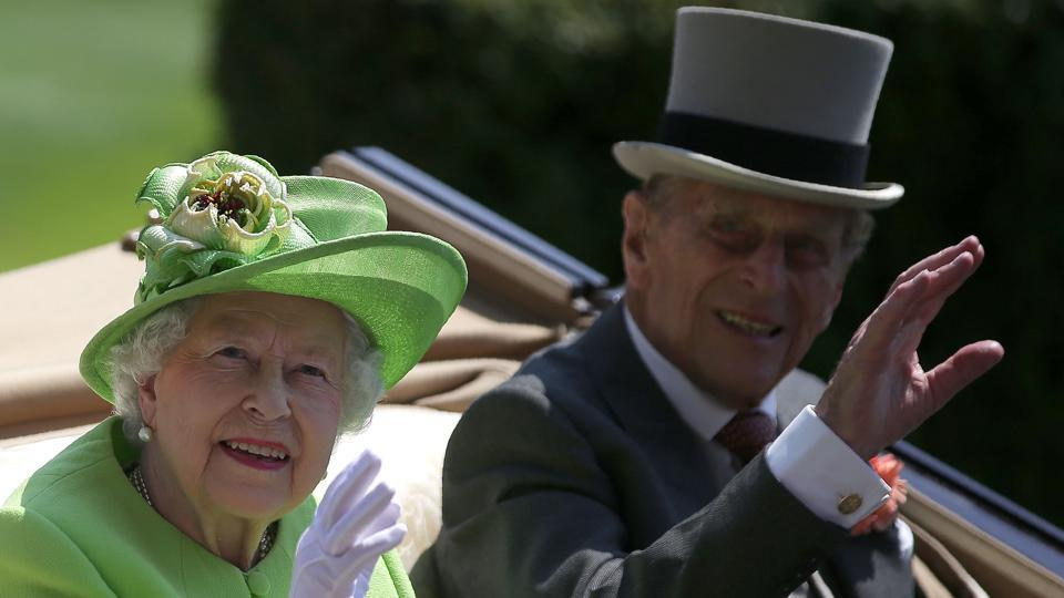 Britain's Queen Elizabeth II and her husband Britain's Prince Philip, Duke of Edinburgh travel by horse-drawn carriage as they arrive on day one of the Royal Ascot horse racing meet, in Ascot, west of London, on June 20, 2017.