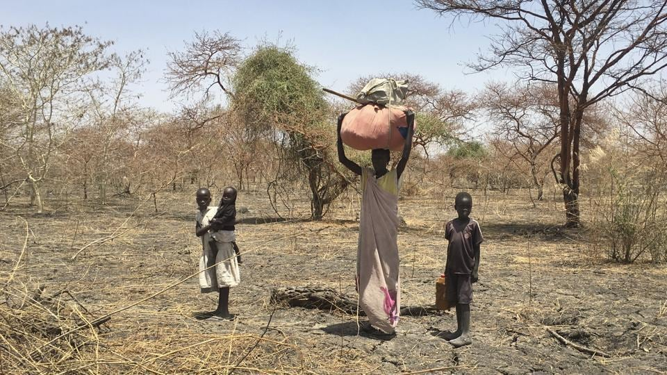 A  displaced family carrying their belongings walks in search of refuge towards the village of Aburoc, South Sudan. A report by Amnesty International says South Sudanese forces burned, shelled and ransacked homes killing civilians and forcing thousands from the Shilluk ethnic minority to flee.  (AP)
