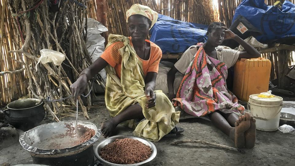 Elizabeth Adwok (L) an ethnic Shilluk who arrived with her seven children in April after having been forcefully displaced from her home three times since South Sudan's conflict began, cooks sorghum in her small hut in the village of Aburoc.  (AP)