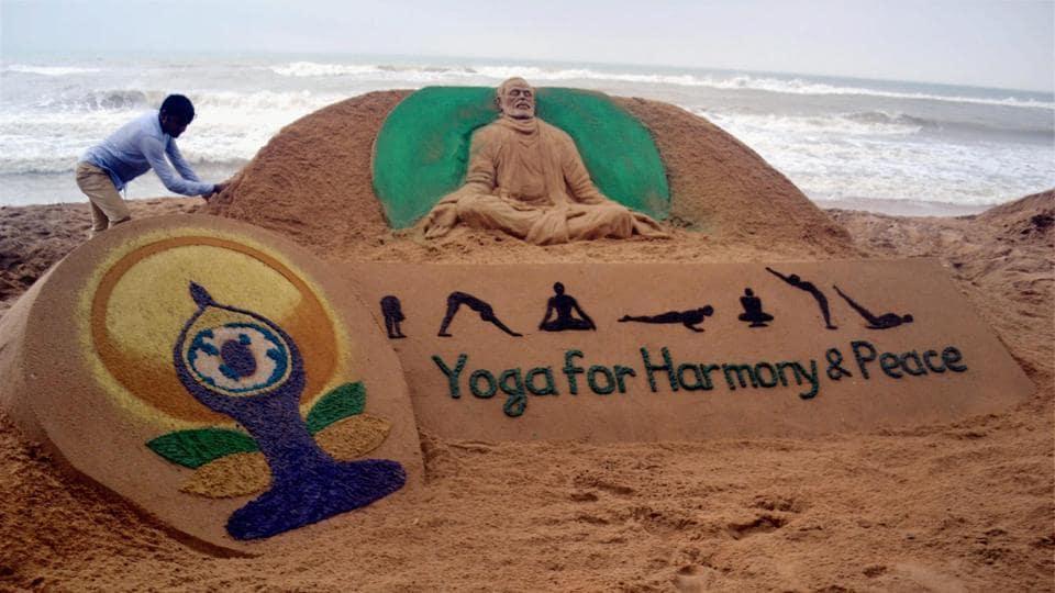 Sand artist Sudarsan Patnaik creates a sand sculpture of Prime Minister Narendra Modi with the message 'Yoga for Harmony & Peace' at Odisha's Puri beach on Tuesday.