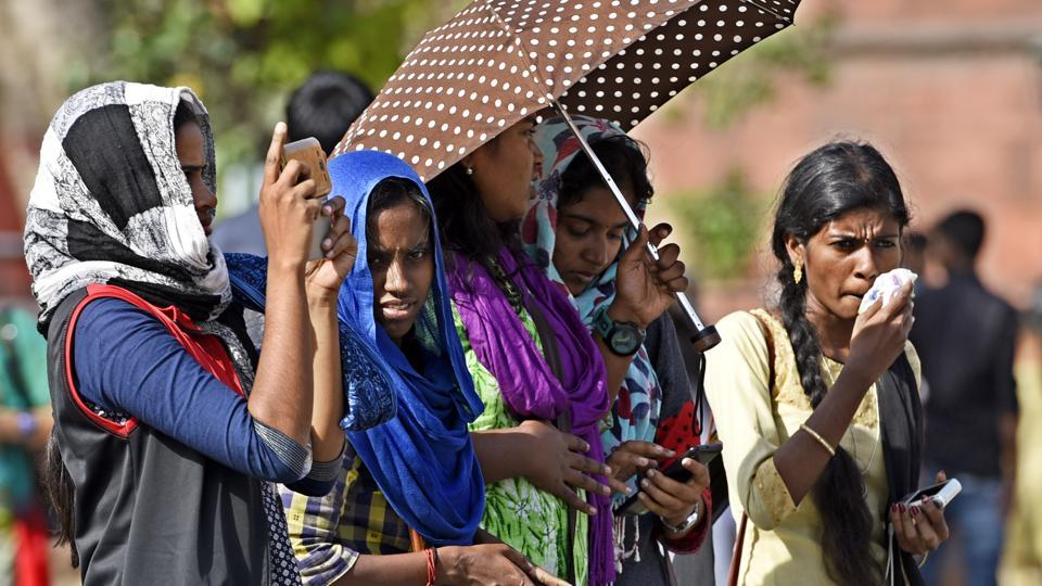 People use scarves and umbrellas to keep the sun away on a hot day in Delhi.