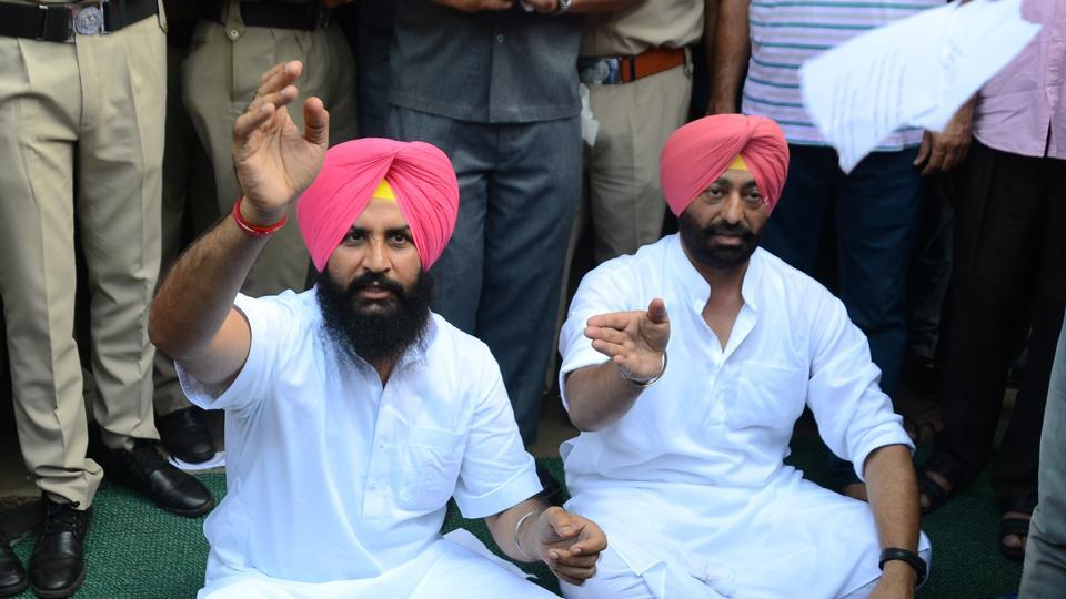 (Left) Lok Insaaf Party (LIP) MLASimerjeet Singh Bains and Sukhpal Khaira protesting outside Punjab Vidhan Sabha gate on Thursday. They were protesting against the denial of permission to enter the assembly complex.  (Sanjeev Sharma/HT Photo)