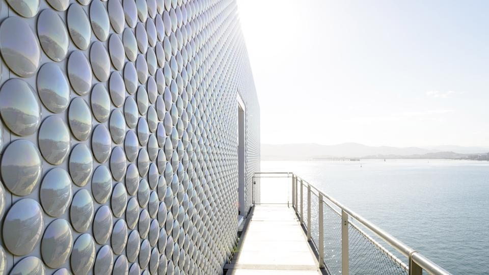 The façade is covered with 2,80,000 rounded, pearly coloured ceramic tiles that reflect the changing colours of the sea and the sky.