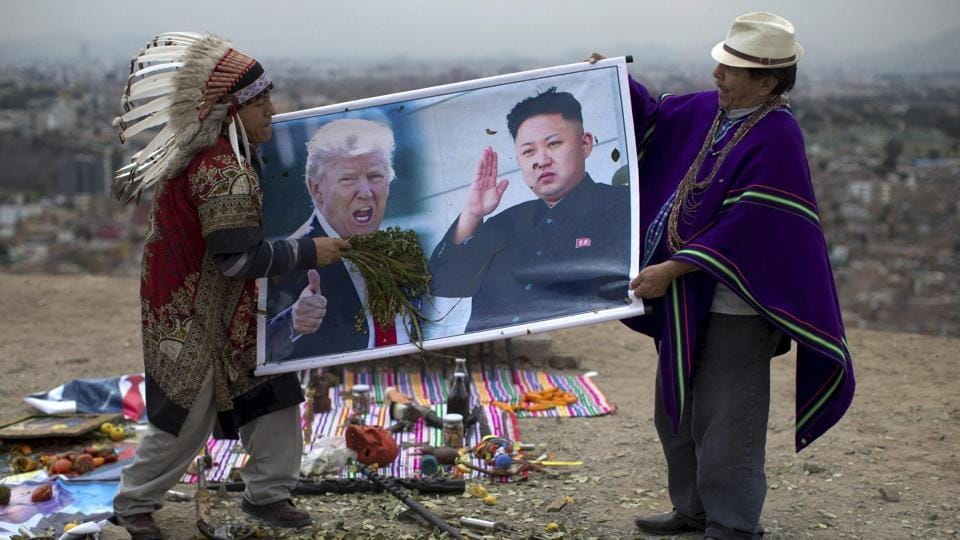 Shamans hold posters of US President Donald Trump, left, and North Korean leader Kim Jong, perform a ceremony on Morro Solar in Lima, Peru, June 12. The shamans said they performed the ritual for peace between the US and North Korea.