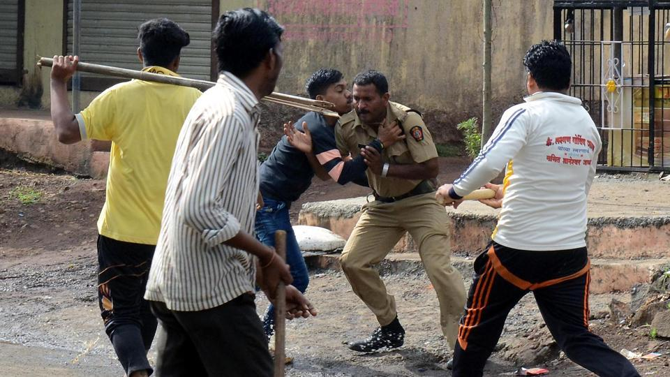 A policeman tries to escape as villagers attack him in Nevali. (Rishikesh Choudhary/HT PHOTO)