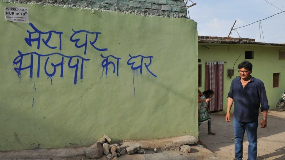 BJP workers paint slogans on the wall of Congress district vice president Pyare Khan`s house in Bhopal, India, on Thursday, June 22, 2017.
