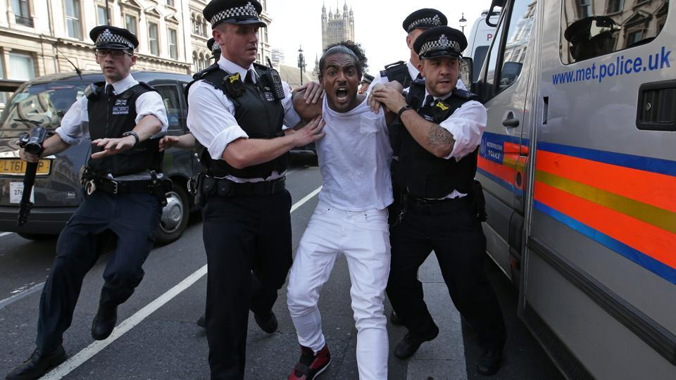 A man is apprehended by police officers as protestors gather in Parliament Square after marching through central London on Wednesday during an anti-government protest to coincide with the State Opening of Parliament and following the deadly fire at Grenfell Tower.