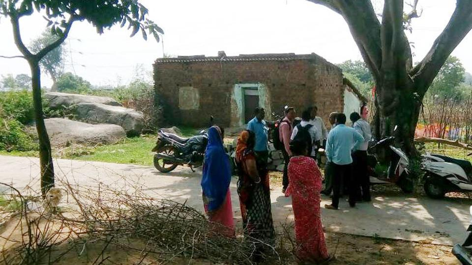 Onlookers outside the house of a farmer who committed suicide in a village.