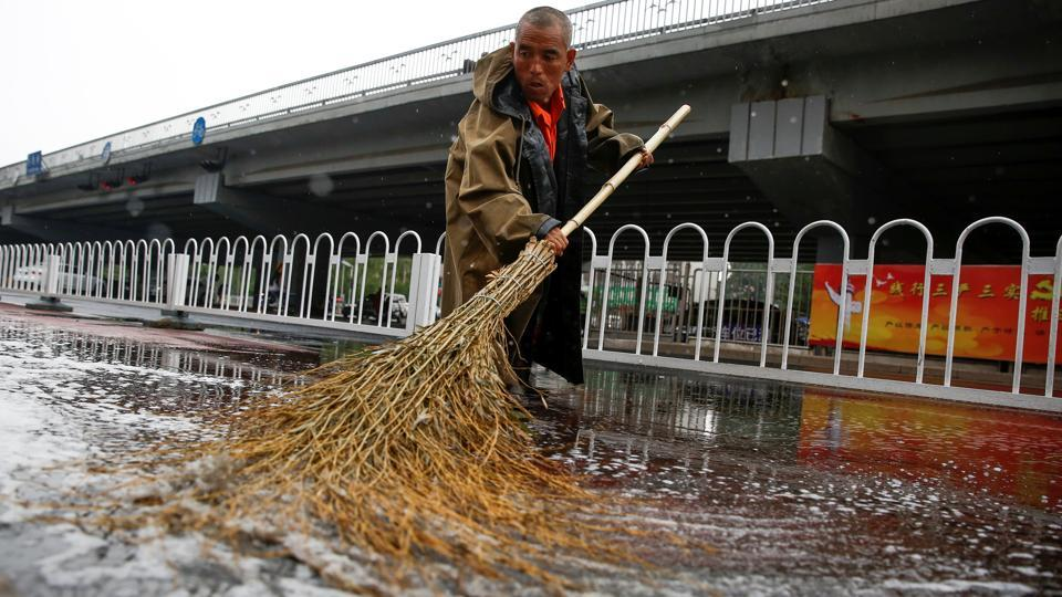 A city cleaner sweeps a street after rain flooded a cycling path in Beijing, China, June 13, 2017.