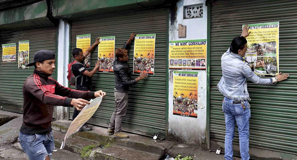 Darjeeling: Activists of GJM paste the party posters on the shutters of close shops during GJM indefinite strike near DM office in Darjeeling on Wednesday. PTI Photo by Ashok Bhaumik (PTI6_21_2017_000360B) (PTI)