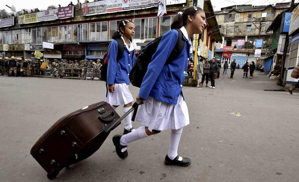 School students walk past security personnel guarding in a street during GJM indefinite strike in Darjeeling, West Bengal on June 21, 2017.  (Ashok Bhaumik /PTI)