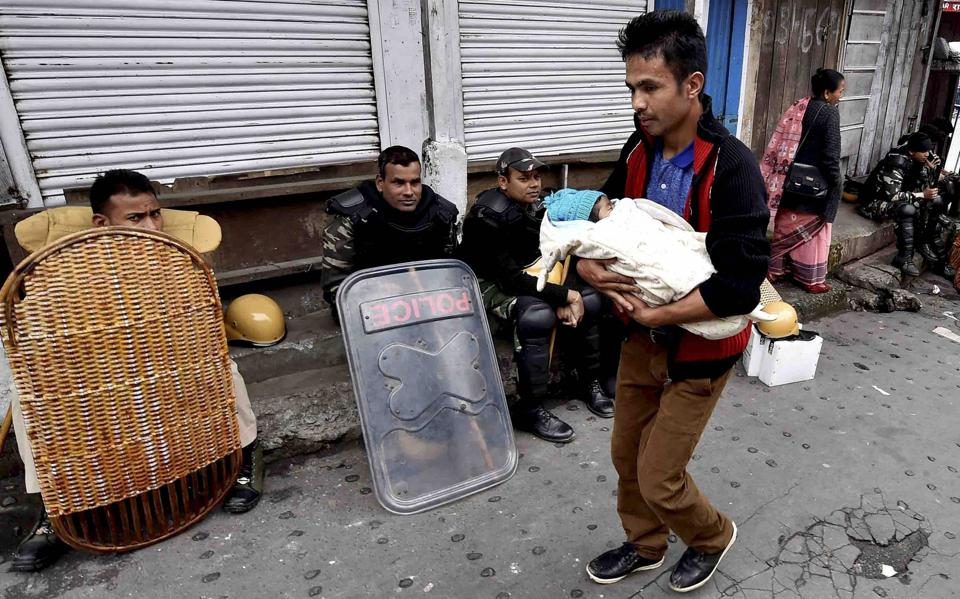 Darjeeling: A man walks past with his new born babby as security personnel guarding in a street during GJM indefinite strike at Chawk Bazar in Darjeeling on Wednesday. PTI Photo by Ashok Bhaumik (PTI6_21_2017_000357B) (PTI)